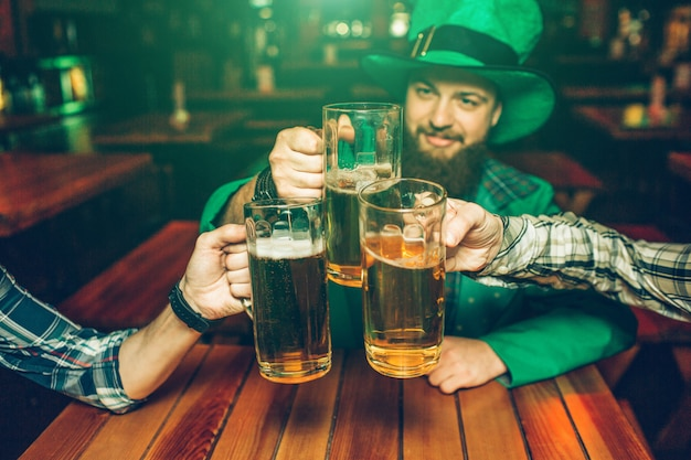 緑の聖パトリックのスーツを着た若い男の写真は、パブで友達とテーブルに座っています。彼らは一緒にビールのジョッキを保持します。