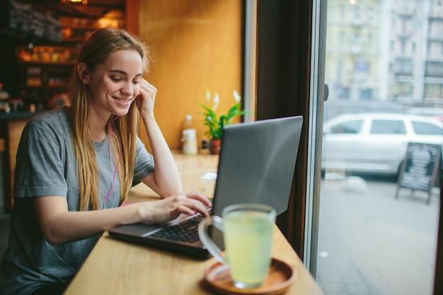 Молодая девушка с ноутбуком слушает музыку в кафе и работает