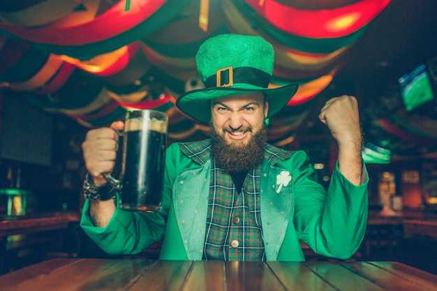 Счастливый молодой человек носит костюм святого патрика. он сидит за столом в баре и держит кружку темного пива. парень выглядит счастливым и взволнованным.