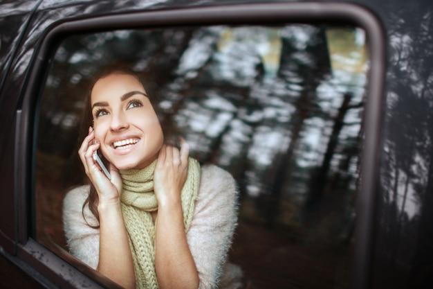Красивая женщина, улыбаясь, сидя на пассажирских сиденьях в машине. девушка использует смартфон