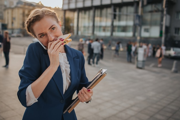 Занятая женщина спешит, у нее нет времени, она собирается перекусить на ходу. работник ест, пьет кофе, разговаривает по телефону, одновременно. предприниматель делает несколько задач.