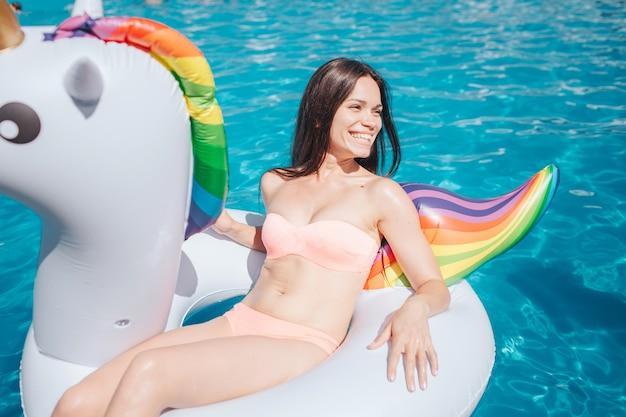しっかりした造りの女の子がエアマットレスに座って、右に見えます。彼女は桃色の水着を着ています。女の子はプールにいます。彼女には休息があります。若い女性が笑っています。