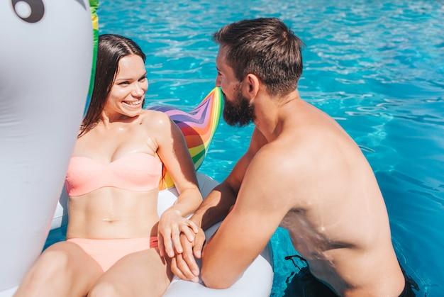 プールで泳いでいる豪華なカップルの肯定的な写真。女の子はエアマットレスの上に横たわっています。彼らはお互いを見て、笑顔になります。男は女の子に傾いています。