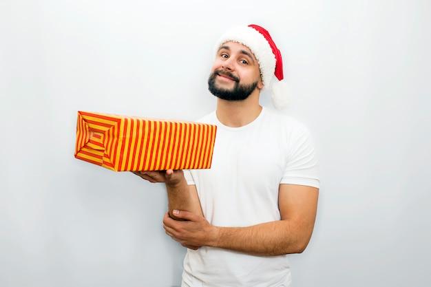 赤い帽子の素敵なひげを生やした男が立って、片方の手でプレゼントをオレンジ色のボックスを保持しています。彼は少し白に分離されたように見え、微笑む。