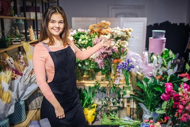 Веселая молодая женщина поза. она улыбается и показывает растения и цветы со стороны. молодая женщина носить черный фартук.