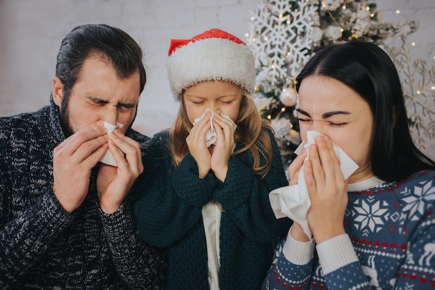 家族はクリスマスに病気です彼らはハンカチを持っています。病気の人は鼻水があります。メリークリスマス、そしてハッピーニューイヤー