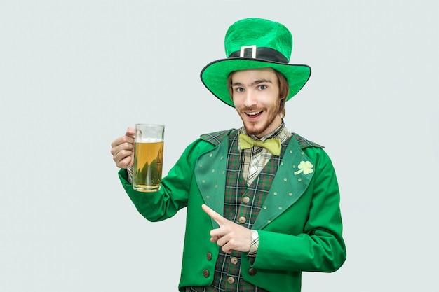 ビールと外観のマグカップを保持している緑の聖パティックスーツで幸せな陽気な若い男。彼はそれを指差して微笑みます。グレーに分離。