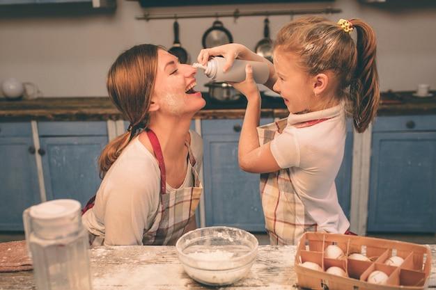 Взбитые взбитые сливки. счастливая любящая семья готовит пекарню вместе. дочь матери и ребенка готовят печенье и веселятся на кухне. раскатать тесто.