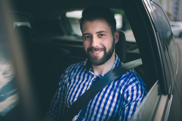 Красивый мужчина улыбается, сидя на заднем сиденье в машине
