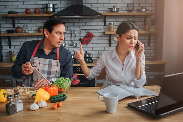 忙しい女性がテーブルに座って電話で話す