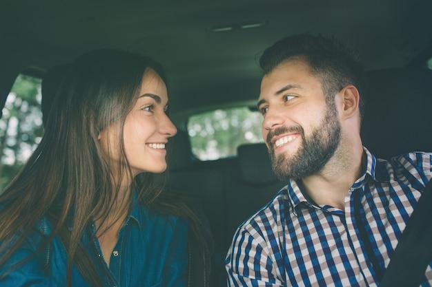 注意深い運転。助手席に座って、ハンサムな男が車を運転しながら笑顔の美しい若いカップル。