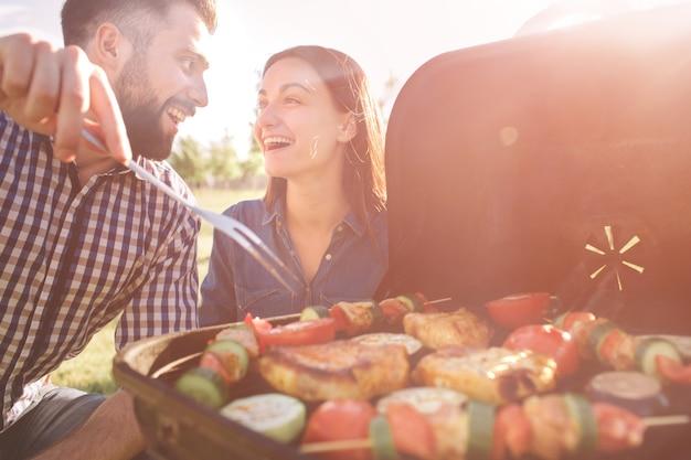 自然の中でバーベキューをしたり、昼食を食べている友人。ピクニック-バーベキューパーティーで幸せな人々で飲食しながら楽しみを持っているカップル。