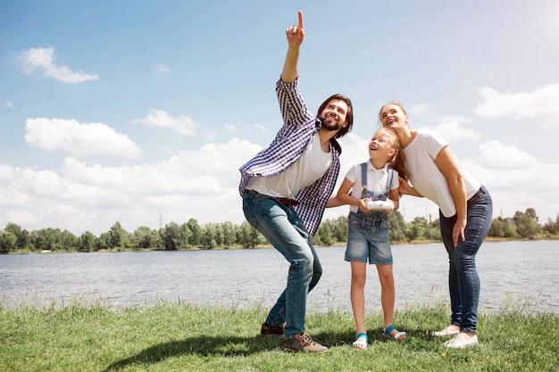 空を見上げている若い家族の素敵な写真。男は上向きです。女の子は手にコントロールパネルを持っています。親は娘の背中を押さえています。彼らは満足している。