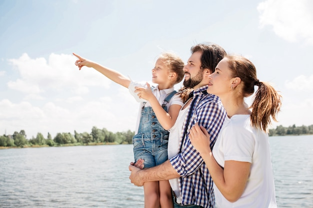 幸せな家族が一緒に立って見上げています。男はこんにちは娘を保持しています。女の子は上向きで前方です。女性は夫の横に立っています。
