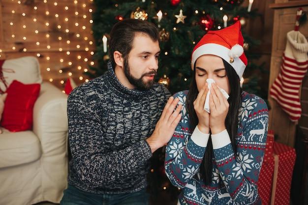 メリークリスマス、そしてハッピーニューイヤー 。若いカップルが自宅で休日を祝います。ハンカチを持つ若い女性。病気の少女の鼻水
