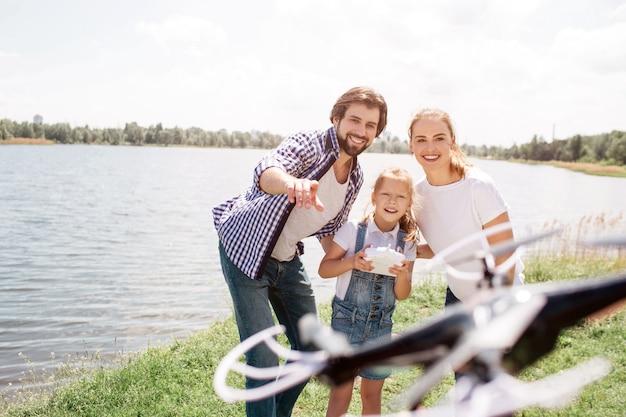 ゴージャスな家族が一緒に立って、写真のドローンを見ています。小さな女の子がコントロールパネルを持っていると笑みを浮かべています。若い男はドローンを指しています。