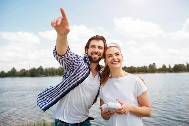 素晴らしいカップルが一緒に立って見上げています。男は妻を抱き締めて上向きです。女性は手にコントロールパネルを持っています。彼らは幸せそうに見えます。