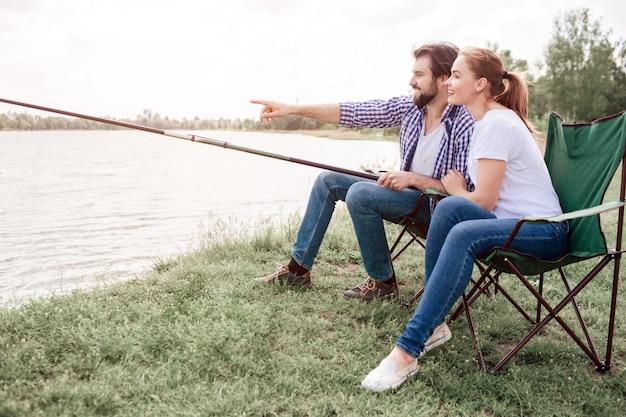 二人は川岸に座っています。男は魚の棒の端を持ち、水を指していますが、少女は男と同じ方向を向いています。彼らはとても穏やかで平和です。