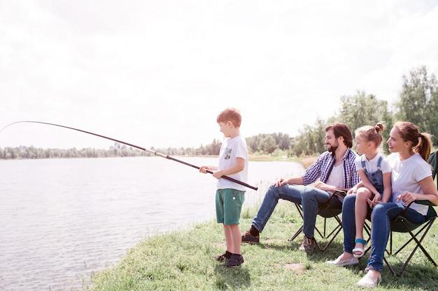 少年は川岸の端に立って、魚の棒を手に持っています。本当に長いです。彼の両親と妹は彼らの後ろに座ってそれを見ています。
