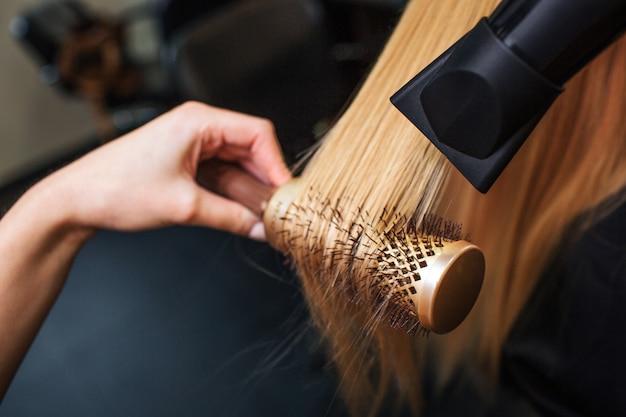 ヘアドライヤーと丸いブラシでブロンドの髪を乾燥する美容師の手のクローズアップ