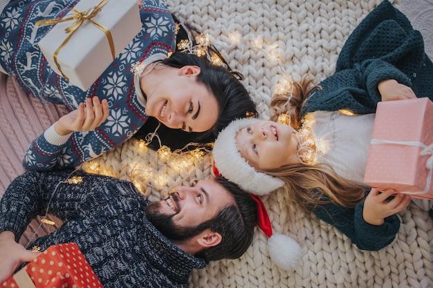 メリークリスマスとハッピーホリデー陽気な母、父と彼女のかわいい娘の女の子が贈り物を交換します。親と小さな子供が屋内でクリスマスツリーの近くで楽しんで。朝のクリスマス。