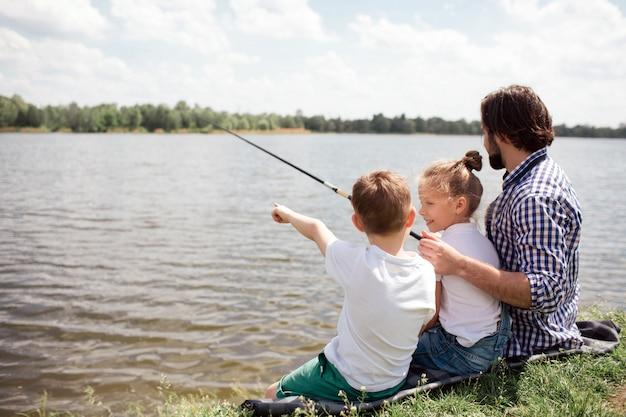Фотография мужчины и его детей, сидящих на берегу реки. парень рыбачит, пока его дети смотрят на него. мужчина держит длинную удочку.