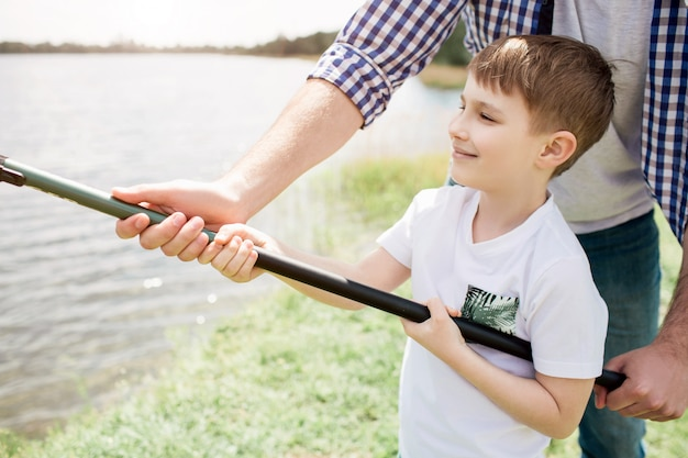 息子が正しい方法で釣竿を保持するのを手伝っている男の写真。少年が両手でそれをしている間、彼は片手でそれを持っています。小さな男は幸せな少年のようです。