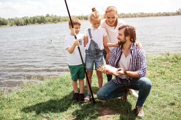 Изображение всей семьи, стоящей на траве и смотрящей на рыбу, которую поймал папа. дети и женщины выглядят изумленными. они счастливы. человек смотрит на них и улыбается.