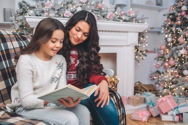 母は娘と一緒に座って本を見てください。彼らはそれを読んだ。女の子は両手でそれを保持します。彼らは装飾された部屋にいます。その背後にはクリスマスツリーと暖炉があります。
