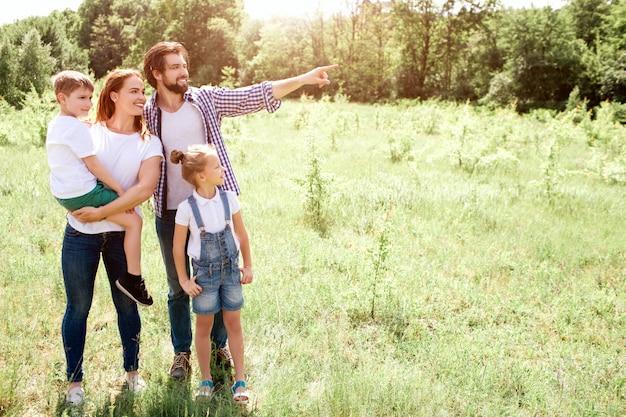 草原に一緒に立っている家族の素敵な写真。お母さんは息子を手に持っています。少女は両親のそばに立っています。ガイはさらに下向きです。