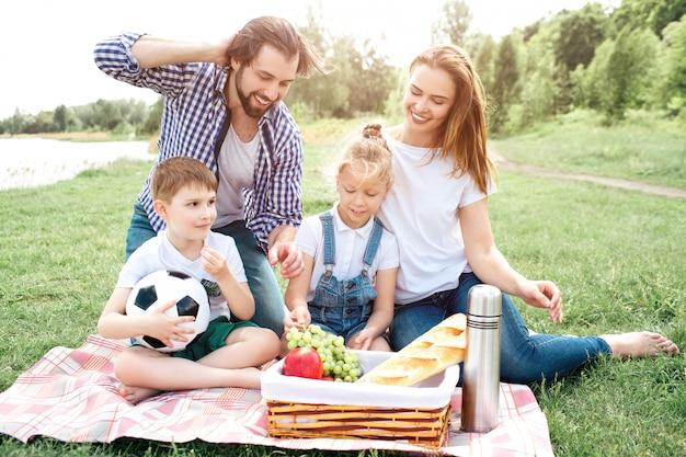 家族は座って、バスケットの食べ物を見ています。彼らはそれを食べたいです。みんな笑顔です。少年は手でサッカーを保持しています。