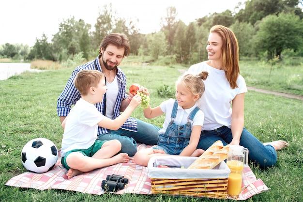 ある家族の人々が一緒に座って楽しんでいます。男は手にリンゴを持っている間、子供たちはブドウを分割しています。女性はそれを見て笑っています。