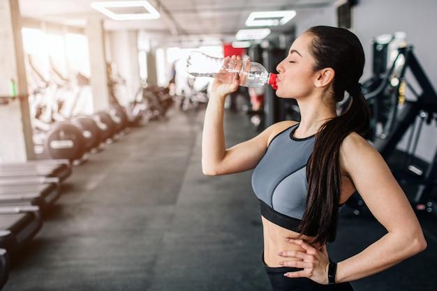 Красивая девушка пьет воду из бутылки