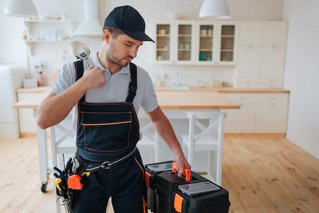 若い男が台所に立って、彼の手でツールボックスを見て