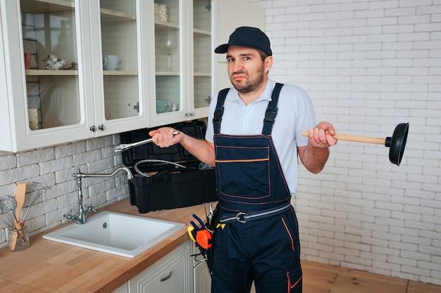 若い便利屋は台所の流しに立つ