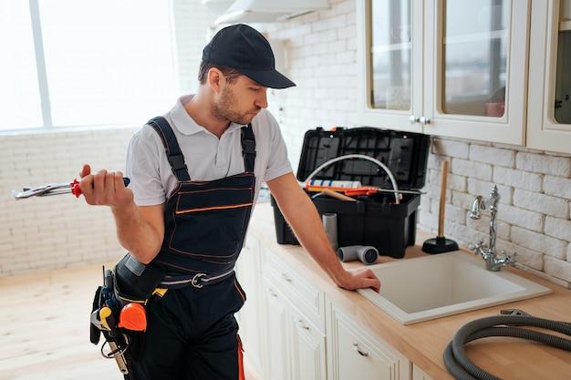 忙しい若い労働者は台所に沈むとそれを見て傾いています