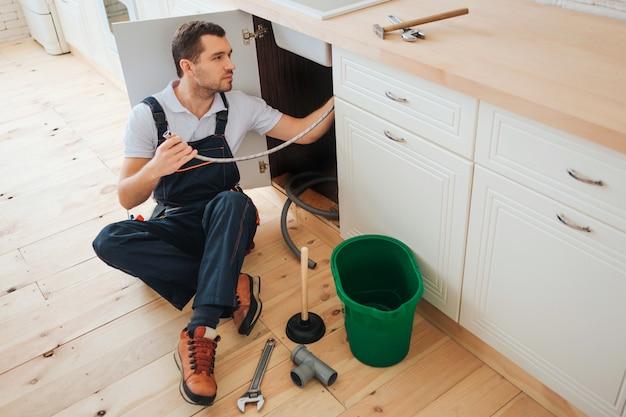 若い便利屋は台所の床に座る