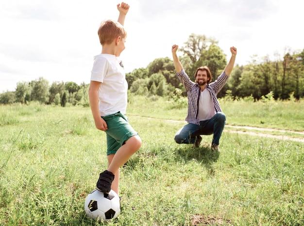 Отец кричит и кричит. он очень рад за своего сына. мальчик играл в хорошую игру. он выиграл. мальчик стоит рядом с отцом и держит мяч с ногой.