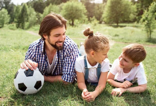 Отец лежит на траве на лугу с детьми. он держит мяч рукой. человек смотрит на сына с дочерью. мальчик выглядит счастливым и веселым.