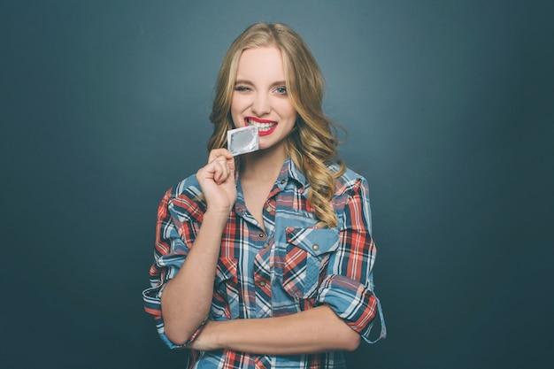 Смешная девчонка кусает пакет с презервативом