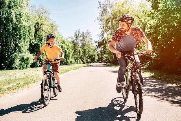 Папа и сын едут на велосипедах