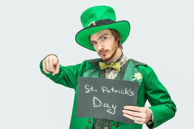 聖パトリックの書き込みで暗いタブレットを保持している緑のスーツの若い男。彼はまっすぐ指さして見ている。グレーに分離。