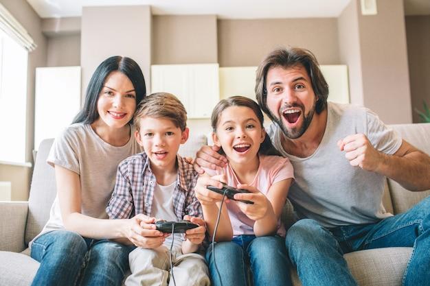 Удивительная семья сидит на диване, играя в видеоигры