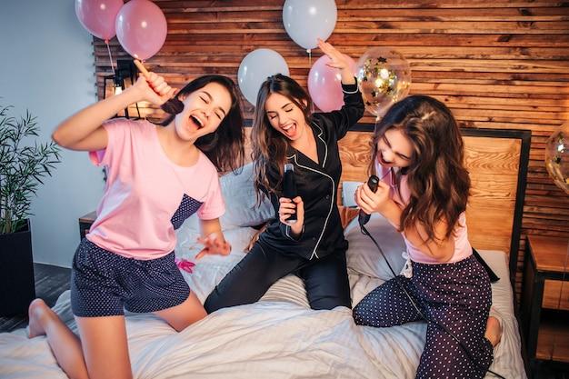Игривые и милые молодые женщины стоят на коленях на кровати в комнате. они делают вид, что поют в микрофонах. женщины держат в руках кисточку для макияжа, аэрозольный баллончик и эквалайзер для волос.