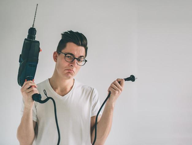 眼鏡をかけている男性がドリルの使い方を知らない