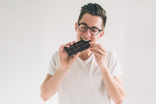 Молодой человек ест шоколад