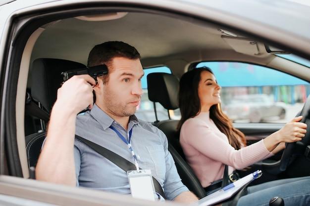 Мужской авто инструктор сдает экзамен с молодой женщиной