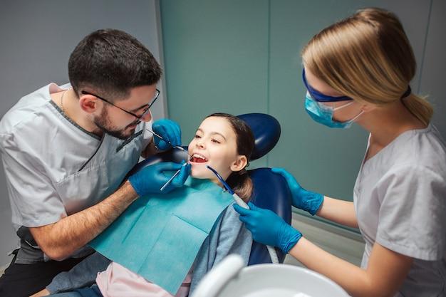 男性歯科医は歯科医のツールで女の子の歯をチェックします。横に立っている女性ヘルパー。部屋の椅子に座っている女の子。彼女は口を開いたままにします。