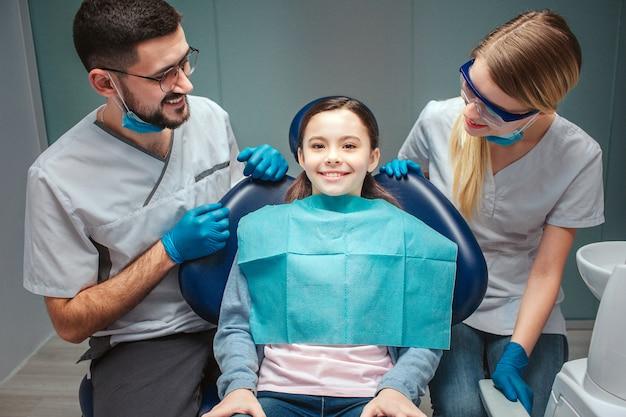 注意深く肯定的な男性と女性の歯科医は子供の患者を見て、笑顔します。歯科用椅子に座っている女の子。彼女はまっすぐに見て笑顔します。緑に分離されました。