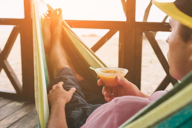 Молодой человек лежа в гамаке на солнечном пляже океаном.